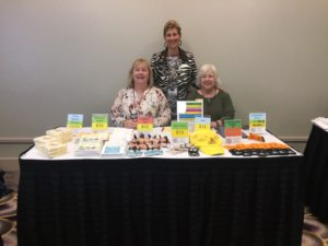 At the conference, Zontians sold Zonta-themed items to help the club operating fund; pictured are Karen Pati (standing, center) with Nancy Dreher (L) and Pam Eccles.